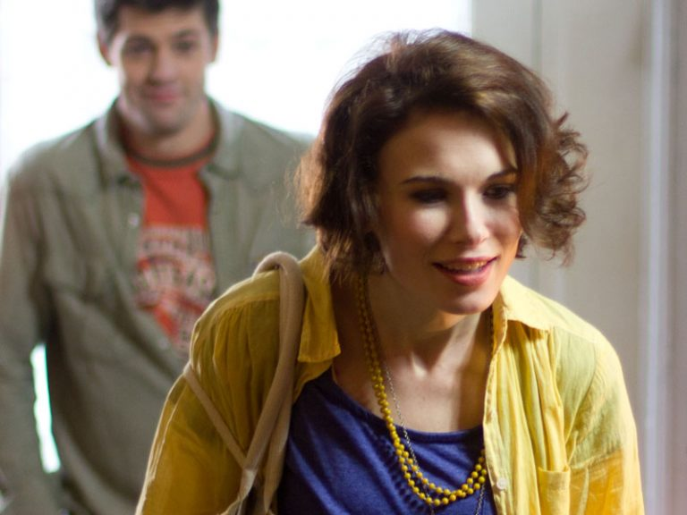 Film still from Stop Eject showing Georgina Sherrington wearing a blue top and yellow blouse.