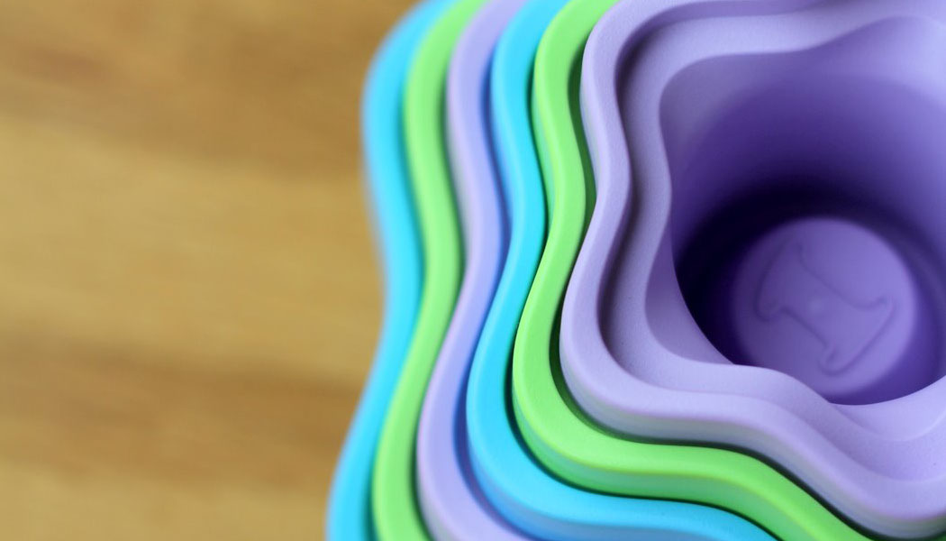 Top down view of green toys recycled plastic stacking cups in purple, green and blue on an oak wooden floor.