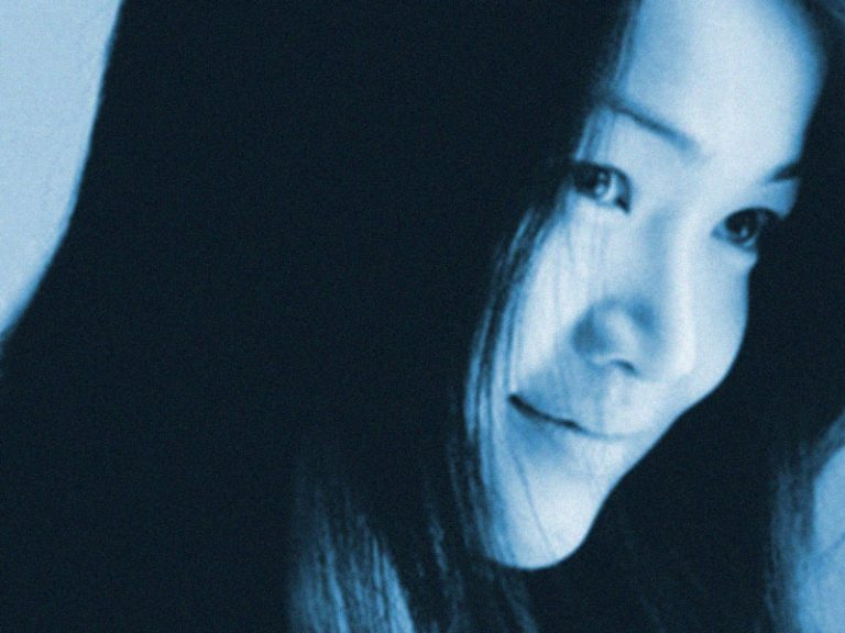 Close-up of smiling asian woman's face with blue tint effect.
