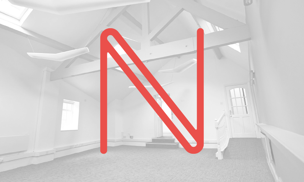 Stylised N in red on a faded black and white photograph of an office interior